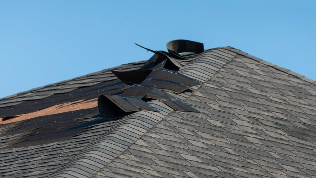 A roof that has wind damage and will require the owner to file an insurance claim for emergency roof repair